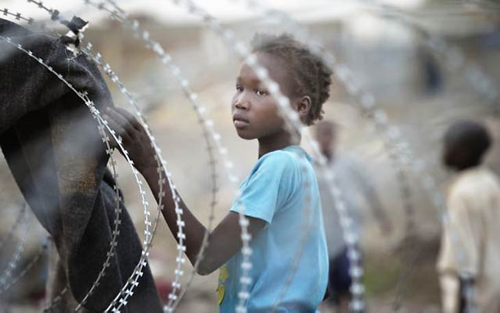 South Sudanese displaced girl behind barbed wire