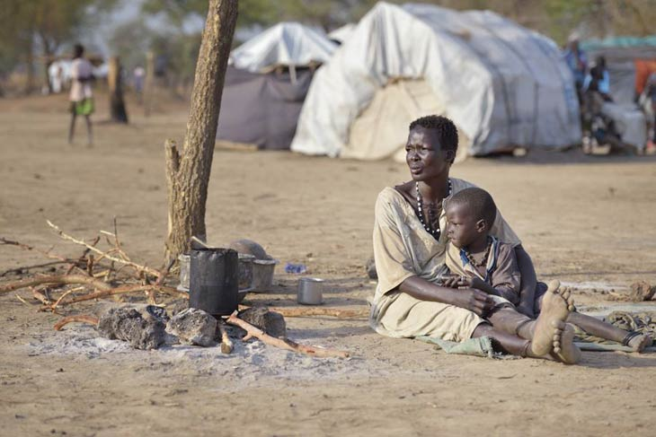 Woman and child sitting on ground in South Sudan camp