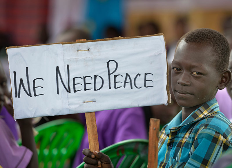 A boy holds a sign at a church-sponsored women's peace rally in Juba, South Sudan. Photo by Paul Jeffrey www.kairosphotos.com